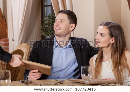 Waiter giving menu to a young couple - stock photo