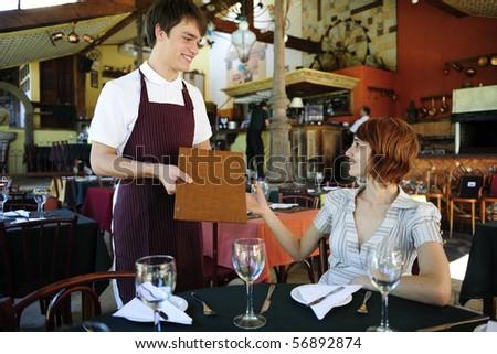 waiter giving menu to female costumer at the restaurant - stock photo