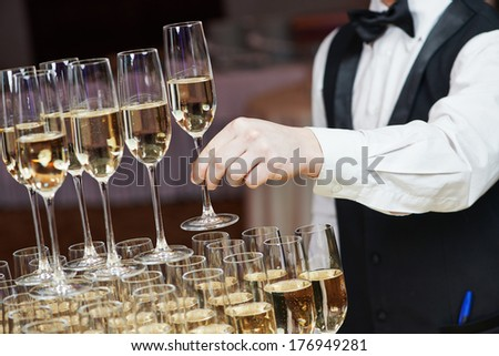 Waiter hand with glass of champagne over pyramid during catering at party - stock photo