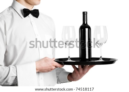 Waiter hands with bottle of red wine and stemware glass on tray - stock photo