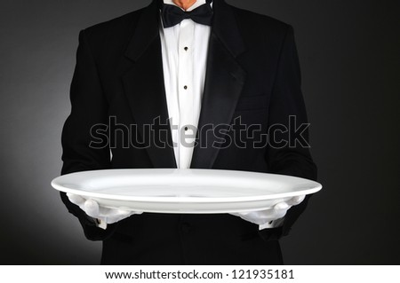 Waiter holding a large white platter over a light to dark gray background. Horizontal format, man is unrecognizable. - stock photo