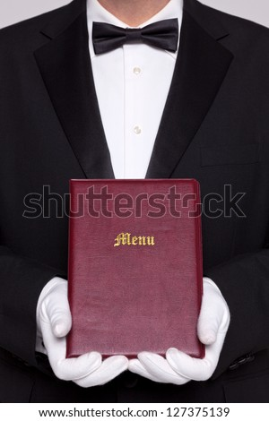 Waiter holding a Menu folder in a restaurant. - stock photo