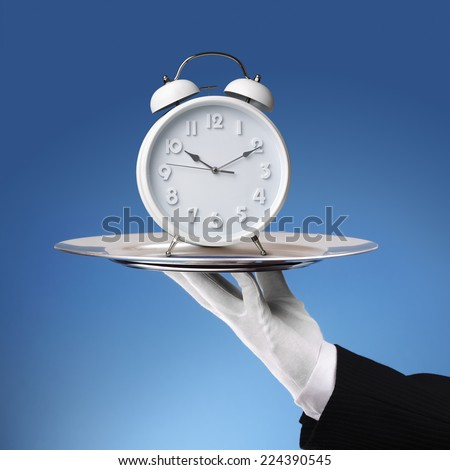 Waiter holding a silver platter with white alarm clock - stock photo