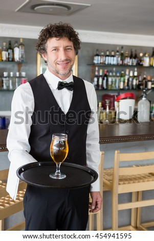Waiter holding a tray with beer glass in restaurant