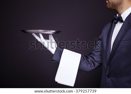 Waiter holding an empty silver tray on black background - stock photo