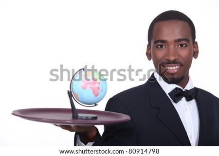 Waiter holding miniature globe on tray - stock photo