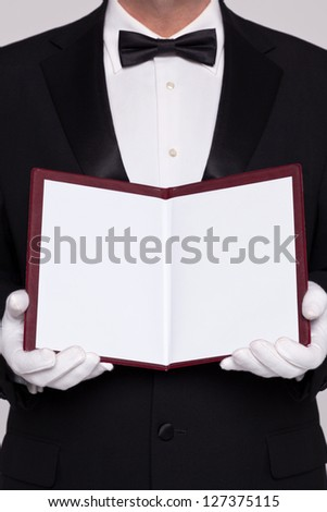 Waiter holding open a blank menu for you to add you own text for food or a wine list. - stock photo