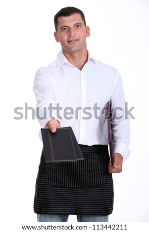 Waiter holding out two menus - stock photo
