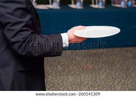 Waiter holding plate - stock photo