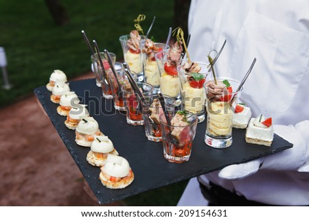 waiter holding plate with appetizer  - stock photo