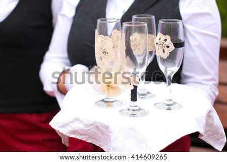 waiter holding tray with four champagne glasses - stock photo