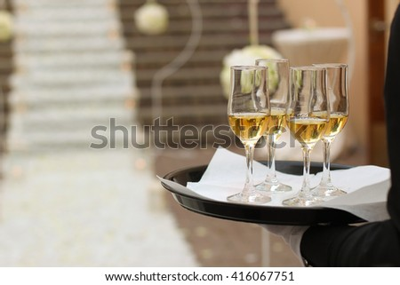 waiter holding tray with four champagne glasses