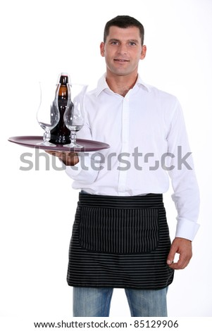 waiter holding tray with glasses and bottle - stock photo