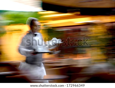 Waiter in a sidewalk cafe holding tea tray for guests - stock photo