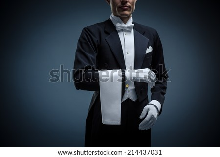 Waiter in a tuxedo on a black background - stock photo