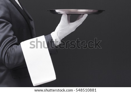Waiter in black suit holding a silver tray over dark background