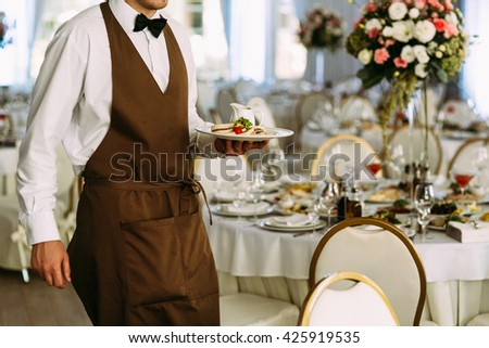 Waiter in the brown outfit serves on the wedding - stock photo