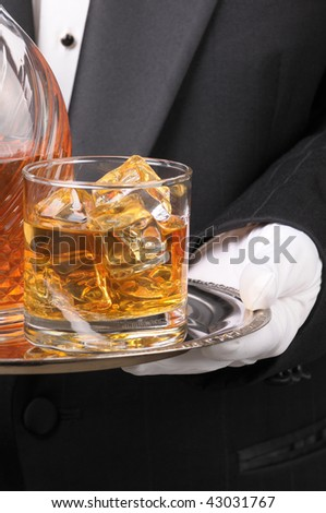 Waiter in tuxedo holding Cocktail and Decanter on tray vertical format torso only - stock photo