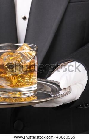 Waiter in tuxedo Presenting Cocktail on silver tray closeup vertical format torso only - stock photo