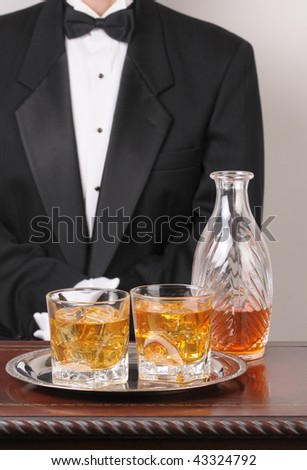 Waiter in tuxedo with Cocktails and Decanter on tray and wood table vertical format torso only - stock photo