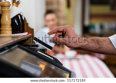 waiter inserts the card into a computer terminal, against visiting the restaurant - stock photo