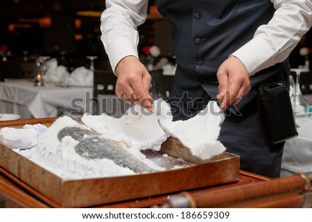 Waiter is carving fish baked in salt crust by restaurant table - stock photo