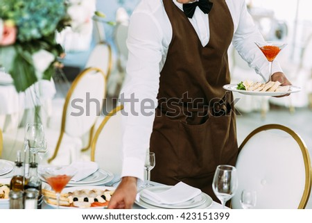 Waiter is serving a wedding table - stock photo