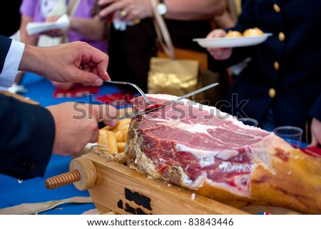 Waiter is slicing Italian raw  ham - stock photo