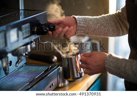 Waiter making cup of coffee at counter in kitchen at cafx92xA9