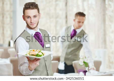Waiter occupation. Young man with food on dishes servicing in restaurant - stock photo