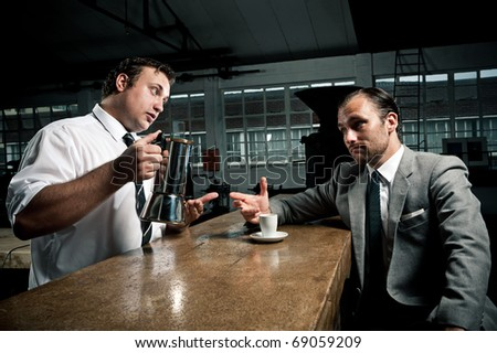 Waiter offers man a refill of fresh coffee from the pot - stock photo