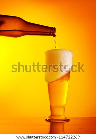 Waiter pouring beer, glass of a cold drink isolated on yellow warm background, festival of beer, Oktoberfest autumn holiday - stock photo