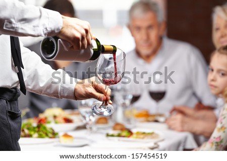 Waiter pouring red wine in a glass at a restaurant table - stock photo