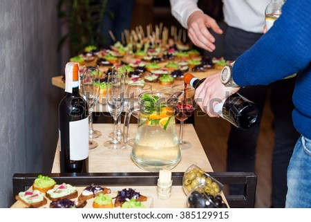 Waiter pouring red wine in a glass at a restaurant table full of appetizers with guests standing near - stock photo