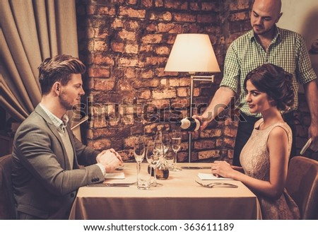 Waiter pouring sparkling wine into glasses to restaurant customers.  - stock photo