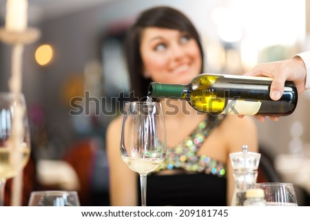Waiter pouring white wine to a beautiful woman - stock photo