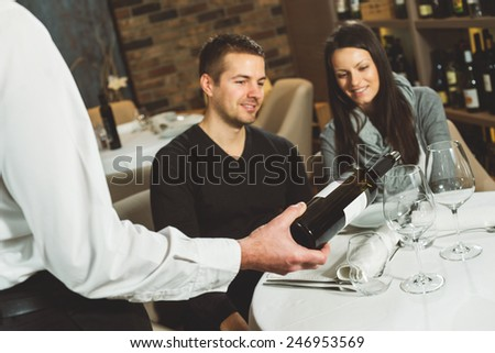 Waiter pouring wine in a glass to a young couple - stock photo