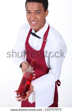 Waiter presenting bottle of wine - stock photo