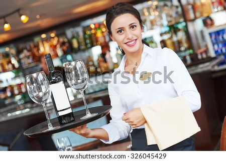 waiter restaurant catering service. Female cheerful worker with tray, glasses and bottle of wine  - stock photo