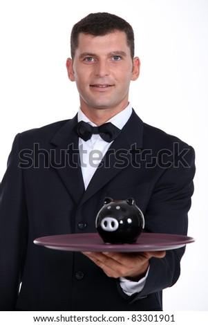 Waiter serving a piggy bank - stock photo