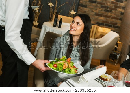 Waiter serving a plate of salad to a woman guest in a restaurant - stock photo