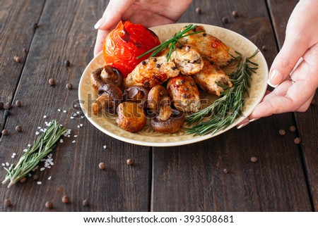Waiter serving a shish kebab with tomato and mushrooms. Chief decorating food for presentation in small cafe. Waiter serving shish kebab with fresh vegetables for retail.  - stock photo