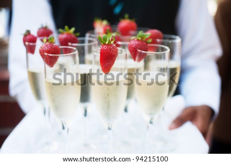 Waiter serving champagne on a tray - stock photo