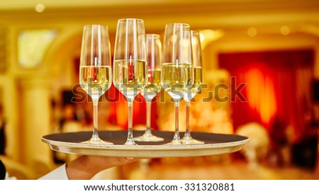 Waiter serving champagne on a tray. Full glasses of champagne on tray - stock photo