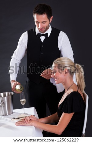 Waiter serving champagne to a beautiful blonde woman seated at a table in an elegant restaurant - stock photo