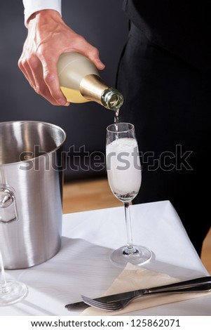 Waiter serving champagne to at the restaurant - stock photo