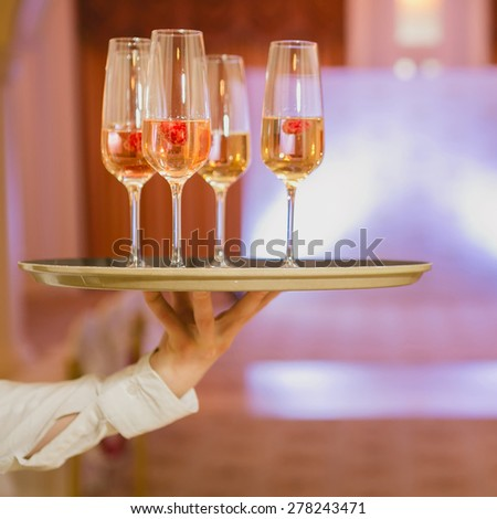 Waiter serving champagne with strawberries on a tray - stock photo