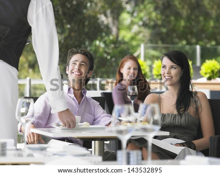 Waiter serving coffee to young couple with woman in background at cafe - stock photo