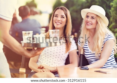 Waiter serving coffee to young women sitting in a outdoors cafe - stock photo