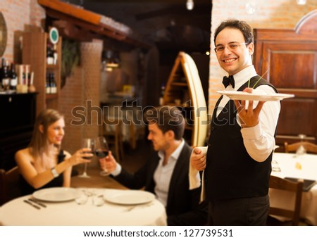 Waiter serving dinner to a couple in a restaurant - stock photo